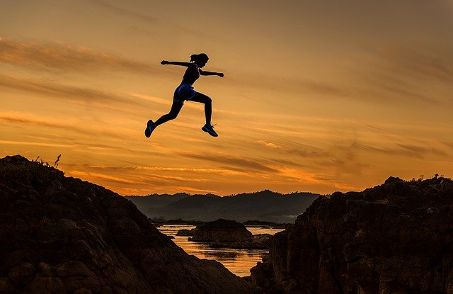 person jumping from mountain to mountain