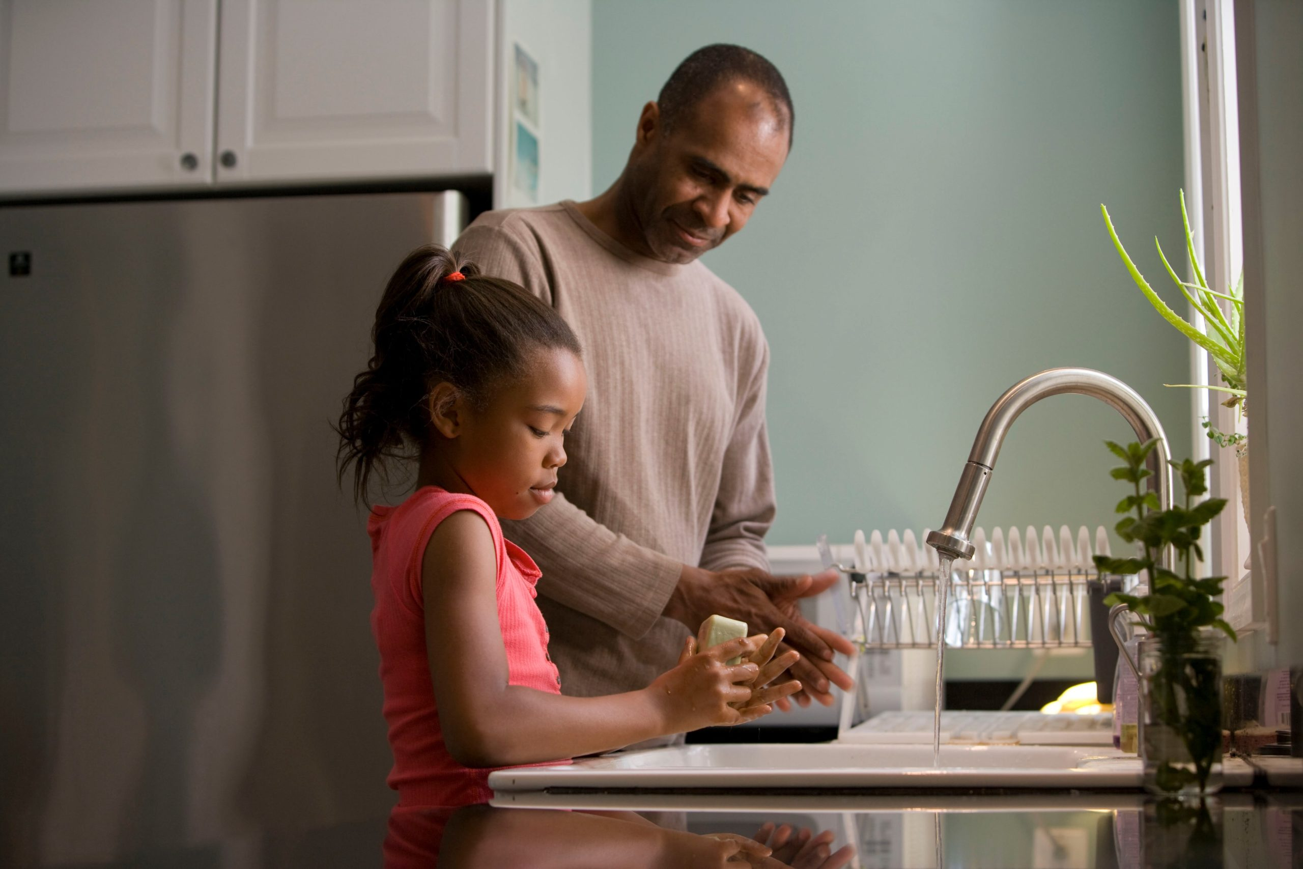 image of father and daughter getting water in a pitcher at the sink