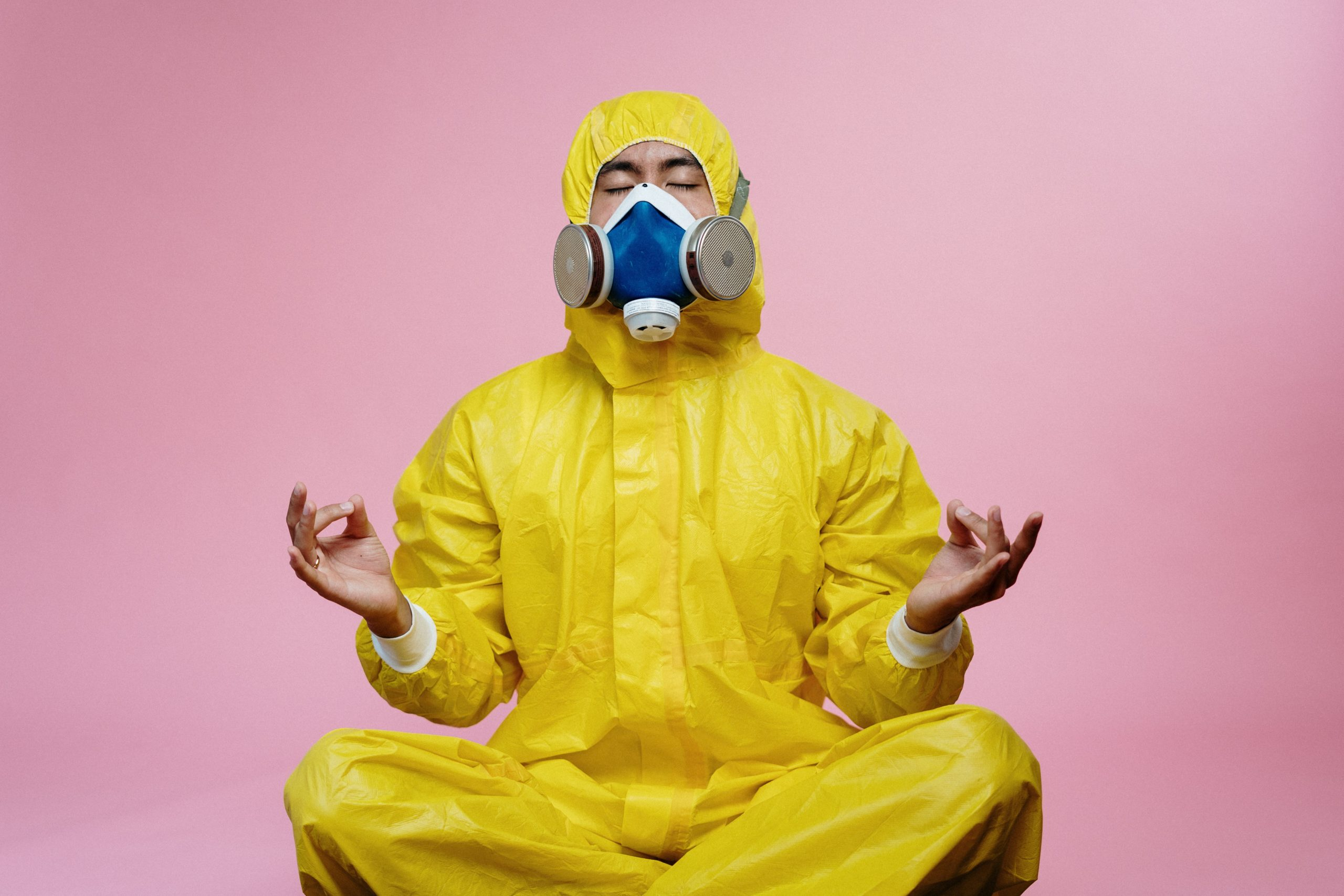 image of man in a germ suit with face mask meditating