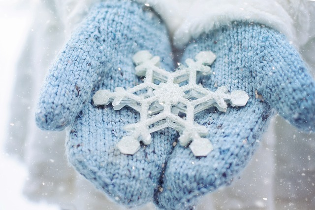 image of blue mittens holding snowflake